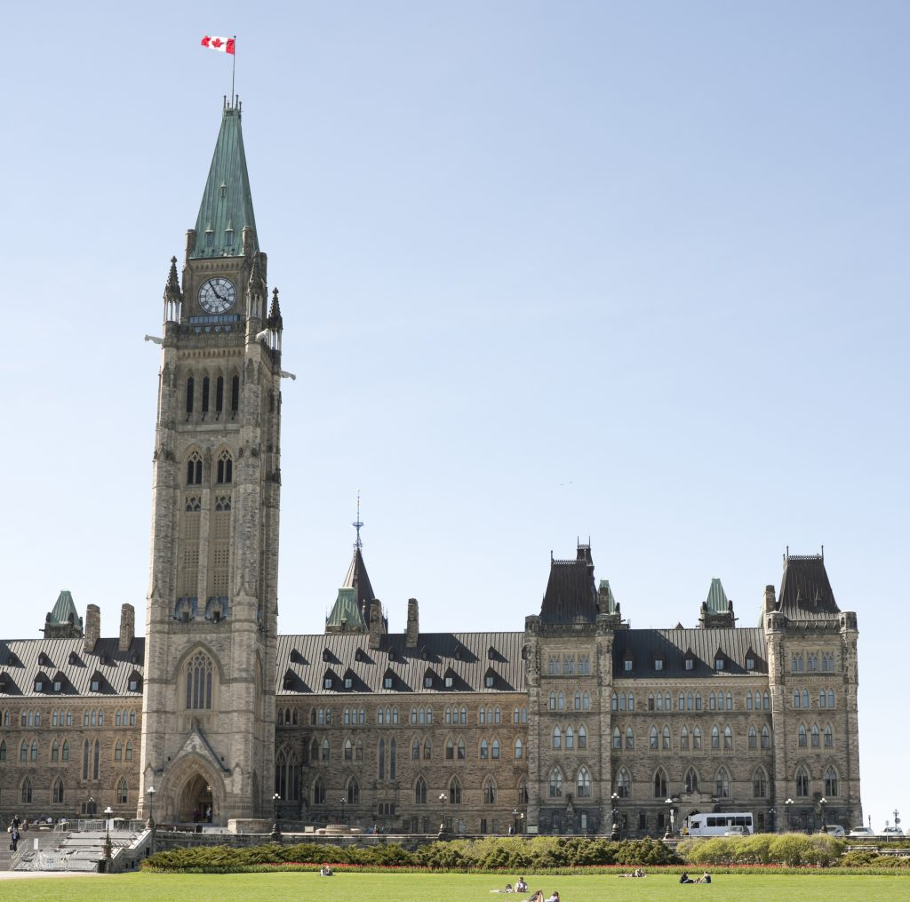 """Ottawa, Canada - May 10, 2011: Canadian Parliament Buildings in spring. Red tulip garden and weekday people traffic on the Parliament grounds."""